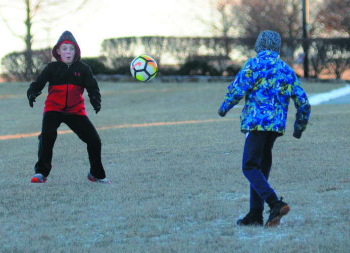 From left: Peyton Girardin, 11 yrs old, takes a pass from Deante Ewell, 12 yrs old, as they play soccer along Braddock Street on a chilly Thursday afternoon in Charles Town. (Journal Photo by Ron Agnir)