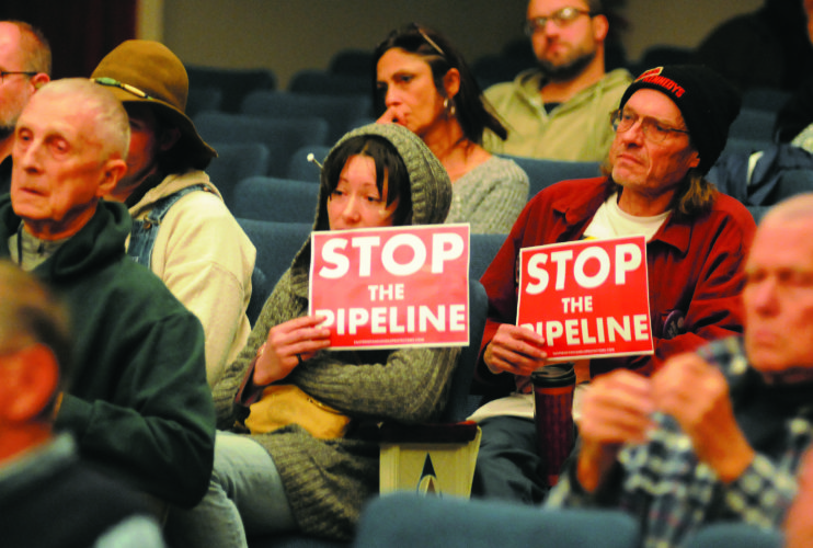 10 Pipeline Hearing2 ra 01-09-18 Two opponents of the Pipeline hold signs at the Public hearing Tuesday evening at Berkeley Springs High School. (Journal Photo by Ron Agnir)