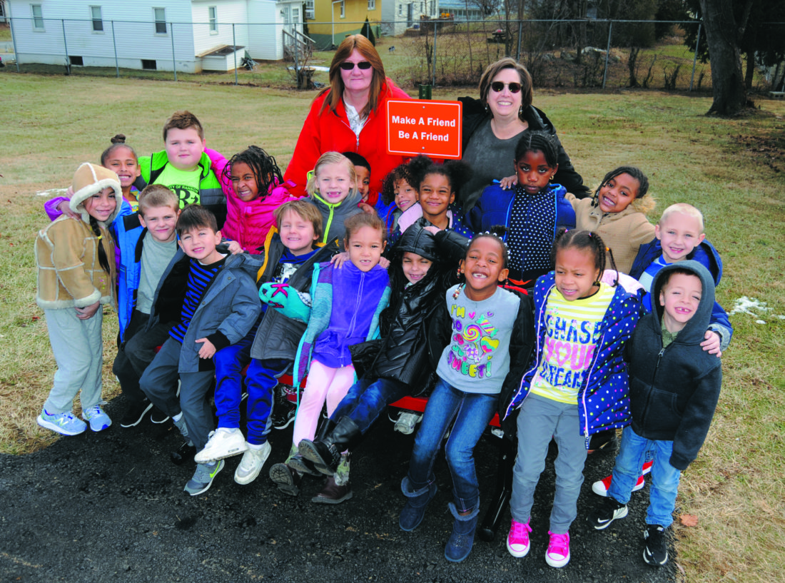 """Journal photo by Ron Agnir Back row, from left are Mrs. Ronda Drummond and Mrs. Anne Miller with their kindergarten class on their Buddy Bench and """"Make a Friend - Be A Friend"""" sign on the Ranson Elementary School playground  Wednesday."""