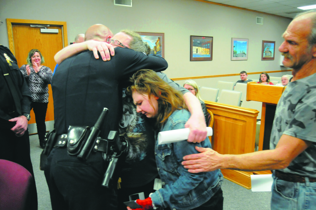 Martinsburg Police School Resource Officer Patrolman James Everhart receives hugs by Martinsburg High School 17 yrs old student Dakota Domer and her parents at the conclusion of a Resolution of Accomplishment presentation Thursday evening at the Regular City Council meeting  in Martinsburg. On Dec. 17, 2017 Patrolman Everhart rushed to the classroom Dakota was at and found her not breathing and unresponsive. Upon placing a radio request for Fire Department Paramedics he detected no pulse and began CPR. Assisted by the School Nurse Rhonda McDaniel and several staff members they performed CPR until EMS arrived with at AED (Automatic External Defibrillation). Dakota was stabilized and rushed to Children's Hospital in Washiington, D.C. (Journal Photo by Ron Agnir)