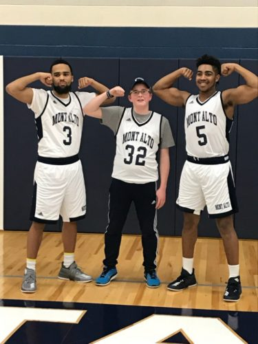 Warm Springs eighth-grader Preston Harris, middle, poses with Penn State Mont Alto basketball players Quionte Harris, left, and Owen Neff after signing with the team in conjunction with Team IMPACT.