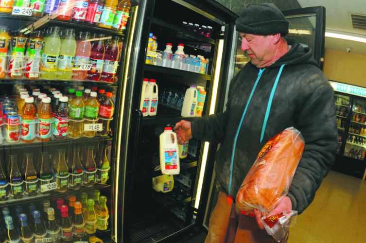 17 Weather-Shop ra 01-16-18 Mike Flagle grabs some milk and bread at Bedington Crossroads Market Wednesday evening. manyt residents prep for the season's first snowfall. (Journal Photo by Ron Agnir)