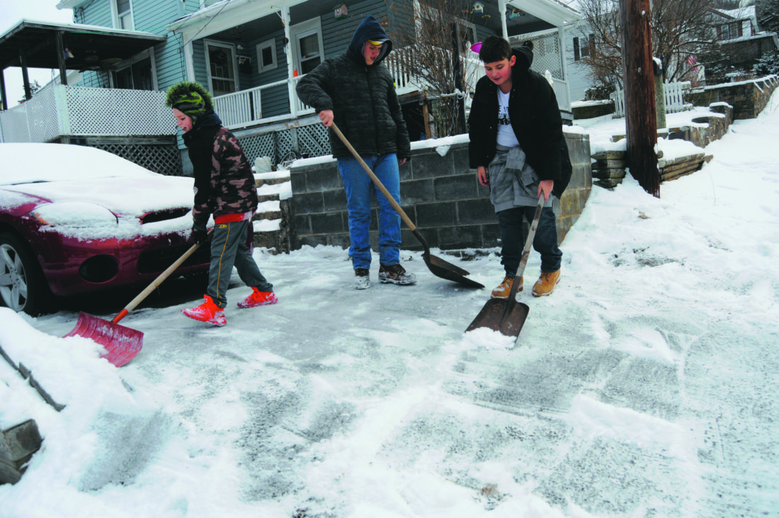 Journal photo by Ron Agnir From left, Eric Penner, 11, Dominik Pearce, 14, and Joseph Williams, 13, shovel snow along Goff Street Wednesday morning in Berkeley Springs. Berkeley Springs got 2-3 inches in Tuesday evening's snow fall. Several schools and offices closed due to the weather.