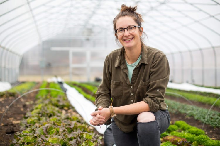 Jenny Quiner, owner of Dogpatch Urban Gardens poses in her greenhouse in Des Moines, Iowa. Dogpatch Urban Gardens is the only for-profit farm in Des Moines city limits — the realization of one of Quiner's dreams. ( AP photo)