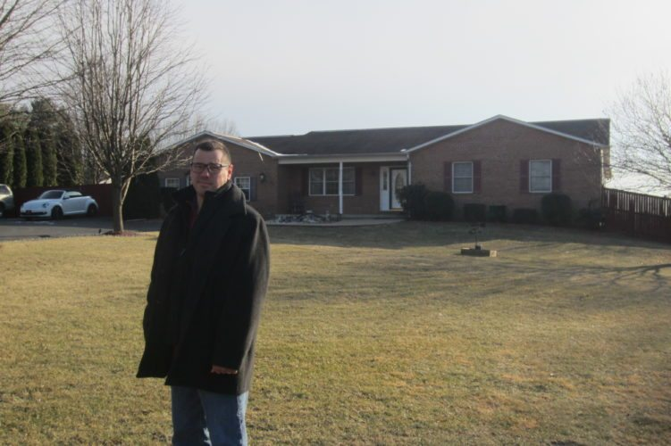 Journal photo by Tim Cook Robert Fluharty stands in front of his Charles Town-area home.