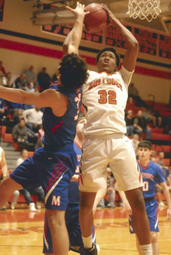 Martinsburg's Corey Barnett puts up a shot against Lamar Haskins of Morgantown during Saturday's win by the Bulldogs. (Journal photo by Eric Jones)