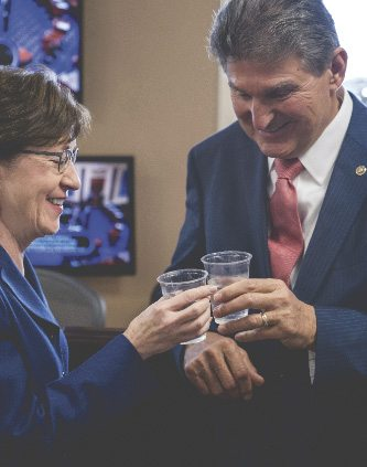 Sen. Susan Collins, R-Maine, left, and Sen. Joe Manchin, D-W.Va., right, clink glasses in a toast to each other as they wait to speak at a news conference on Capitol Hill in Washington, Monday. (AP photo)