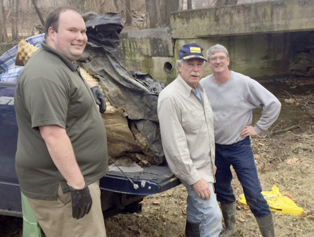 """Chad Minnick, Martinsburg stormwater coordinator; """"Capt."""" Lou Scavnicky, Opequon Creek Project Team; and Clint Hogbin, chair, Berkeley County Solid Waste Authority, were among several volunteers who picked debris out a short stretch of Tuscarora Creek in Martinsburg on Monday. They are standing next to a truck load of debris that came from under the bridge behind them. (Submitted photo)"""