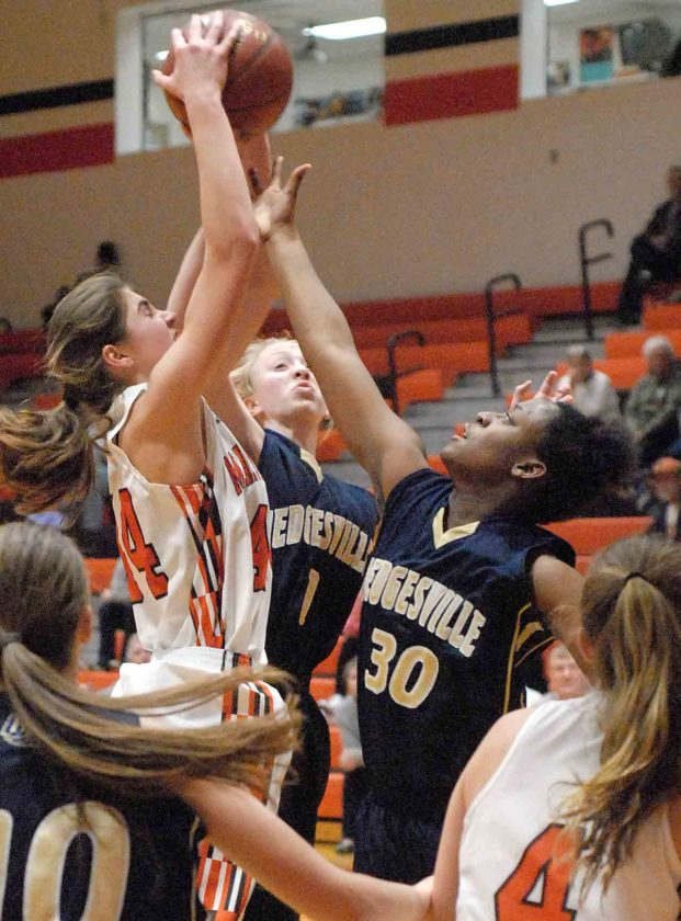 Martinsburg's Morganne Andrews (44) outleaps Hedgesville's Meghan Kearns (1) and Desirae Hosby (30) for the ball Thursday night. See more photos on CU.journal-news.net. (Journal photo by Eric Jones)