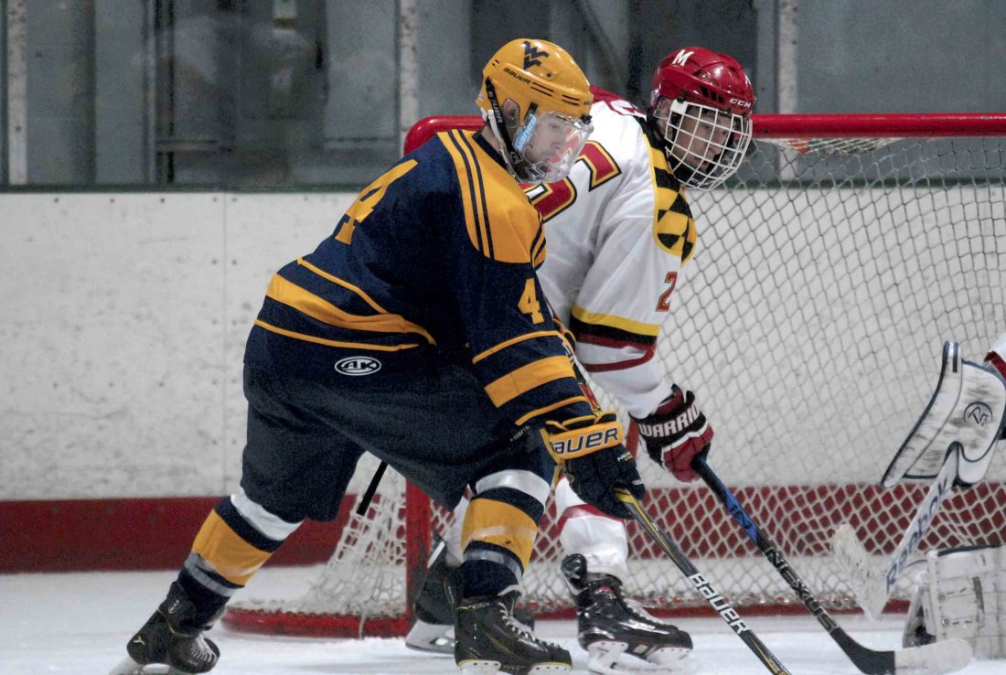 Jake Cooper of the West Virginia Division II club hockey team digs in front of the net with a defender from Maryland during a game last week. Four players from the Eastern Panhandle are on the WVU team. (Journal photo by Rick Kozlowski)