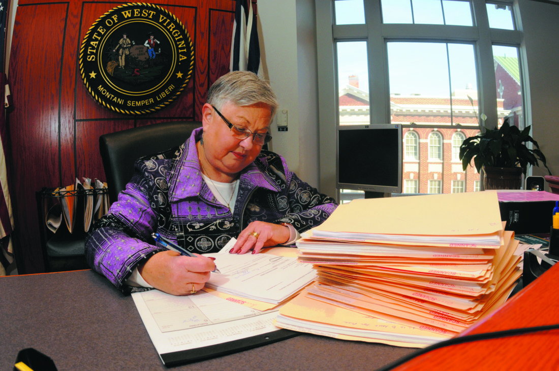 Journal photo by Ron Agnir Jefferson County Magistrate Court Judge Gail Boober reviews over 40 cases at her desk Friday morning. This is an average workload, according to Boober.