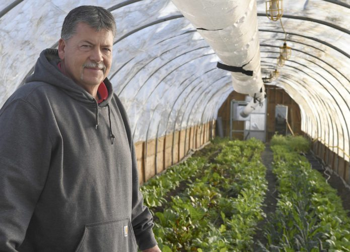 Bert Jones poses for a photo inside Living Hope Farm's greenhouse in Bristol, Wis. While other farmers wait out the winter,  Jones, the manager of the farm, is growing and harvesting despite the weather.  (AP photo)