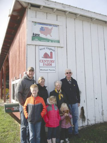 Three generations of the Michael family stand at their new plaque designating their farm a West Virginia Century Farm. From left is, Brad and Beth Michael with children Grant, Ava, and Lily, Brad's parents Jackie and James Michael. (Photo courtesy of Tricia Lynn Strader)