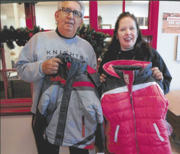 From left, Bob Rizzo, Knights of Columbus secretary of Council 13887, and Amy Chrisman, a guidance counselor at Shepherdstown Middle School, hold up some of the coats that were donated.