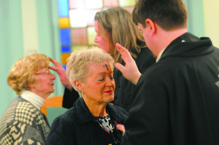 Rev. Matt  Day, applies an ash cross to Catherine Neel  Wednesday at the noon service at St. John's Lutheran Church in Martinsburg. Ash Wednesday is a Christian day for peace and the first day of Lent, which is six weeks of repentance before Easter. (Journal Photo by Ron Agnir)