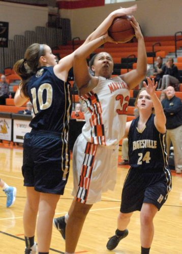 Journal photo by Eric Jones Martinsburg's Kyaira Page, middle, puts up a shot while being defended by Hedgesville's EmilyBethel, left, and Serenity McDill during Monday's Class AAA, Region II, Section 1 game in Martinsburg.