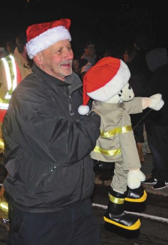 Perth Volunteer firefighter Edwin Leonard holds a fire dog puppet while participating in the annual Broadalbin Christmas Parade in the Village of Broadalbin on Nov. 28. (The Leader-Herald/Bill Trojan)