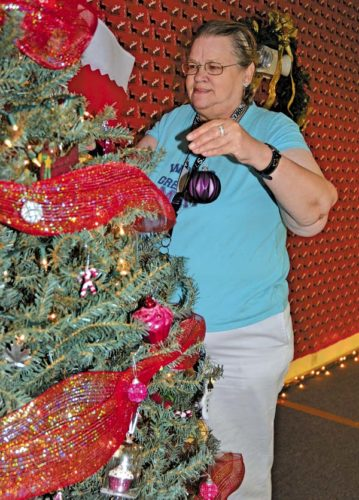 Laura Wooster of Gloversville places an ornament on one of the Christmas trees at the Gloversville Senior Center on Thursday. (The Leader-Herald/Bill Trojan)