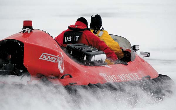 In this Feb. 13 photo, rescue crews use a hovercraft to search the frigid waters of Conesus Lake in Livonia for two missing snowmobilers who are believed to have fallen through the ice. (The Associated Press)