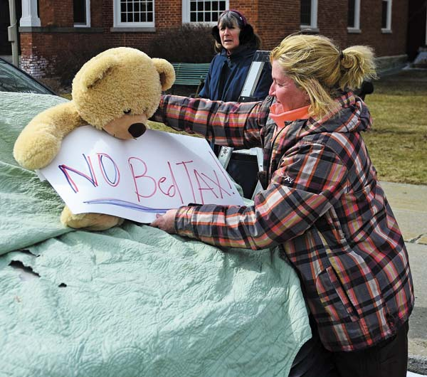"Trish Isabella, the leader of Monday's protest, thinks the ""bed tax"" is unbearable, so she lets her plush friend do the talking for her in front of North William Street in Johnstown. (The Leader-Herald/Bill Trojan)"