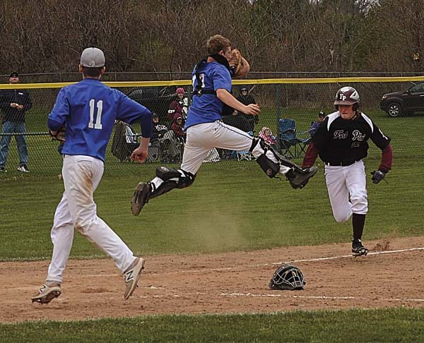 Schoharie catcher Mitchell Barton leaps for a high throw as Fort Plain's Cameron Dillenbeck looks to score after being caught in a rundown on a pickoff attempt during the fifth inning of Wednesday's Western Athletic Conference game at the Fort Plain Sports Complex. (The Leader-Herald/James A. Ellis)