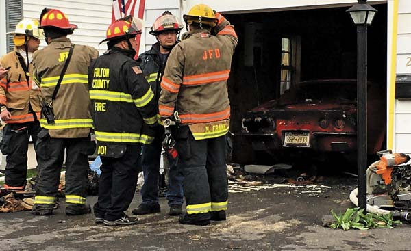 Firefighters discuss the cause of a fire at 214 North Chase St. in Johnstown on Thursday afternoon that damaged the garage and a 1973 Corvette parked inside of it.  (The Leader-Herald/Al Vieira)