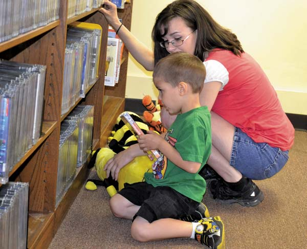 Joseph Nolan and Cassandra Donofrio check out the  children's video section at the Gloversville  Public Library's temporary  location in the Center for  Regional Growth building,  34 W. Fulton St., on Monday.  The library is  expected to be housed there for up to two years.   Photo by Kerry Minor The Leader-Herald