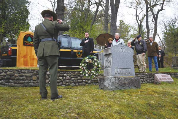 Forest ranger Capt. John Streiff, along with several retired rangers and their families, salutes the grave of Ranger James Ahern Sunday afternoon at Pine Ridge Cemetery in Saranac Lake. Sunday was the 100th anniversary of AhernÕs death, the first line of duty death for the forest rangers. (Enterprise photo/Justin A. Levine)