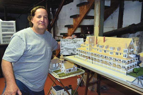John Wheeler kneels next to the scale model version of Saranac LakeÕs old Riverside Inn that he spent seven months building. ÒRemember When?Ó an exhibit of WheelerÕs models of historic Saranac Lake buildings, opens today at the Saranac Laboratory Museum on Church Street. (Enterprise photo/Chris Knight)