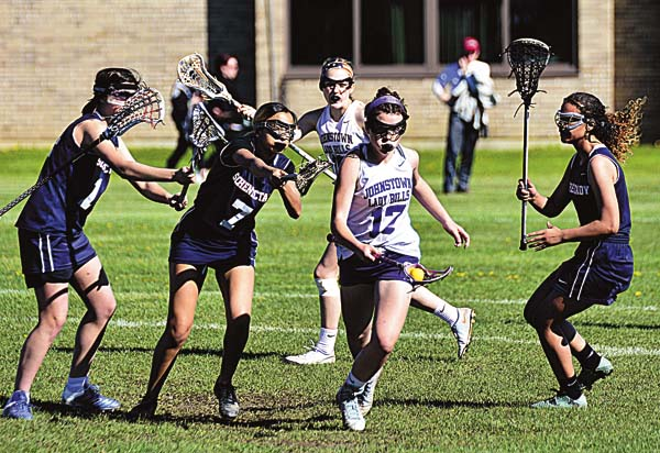 Schenectady's Monite Jolivert checks Johnstown's Mango Delgado (17) as she splits defenders during Thursday's non-league lacrosse match at Johnstown High School. (The Leader-Herald/Bill Trojan )