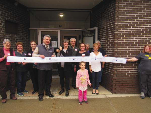 At center, Mark Kilmer, president and CEO of the Fulton Montgomery Regional Chamber of Commerce, and Barbara LaDonna, director of the Gloversville Public Library, get ready to cut the ribbon opening the library's temporary location at 34 W. Fulton St. Saturday. They are supported, from left, by Chris Ressess, library board president; Patty Franco, a member of friends of the library;  Jan LaPorte, library staff;  John and Jenny Mazur, library Friends;  Linda Conroy, library staff; Carole Gottung, a friend; and Circe Johnson, staff. In front is Saya Moran, right, and Paige Morehouse, right, both library patrons from Gloversville. (The Leader-Herald/Eric Retzlaff)