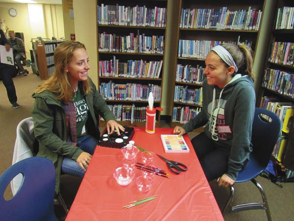 Alexandra Franco, a senior at Ballston Spa High School, and Madison France, a freshman, prepare supplies for face-painting children during the library opening as a National Honor Society project. (The Leader-Herald/Eric Retzlaff)
