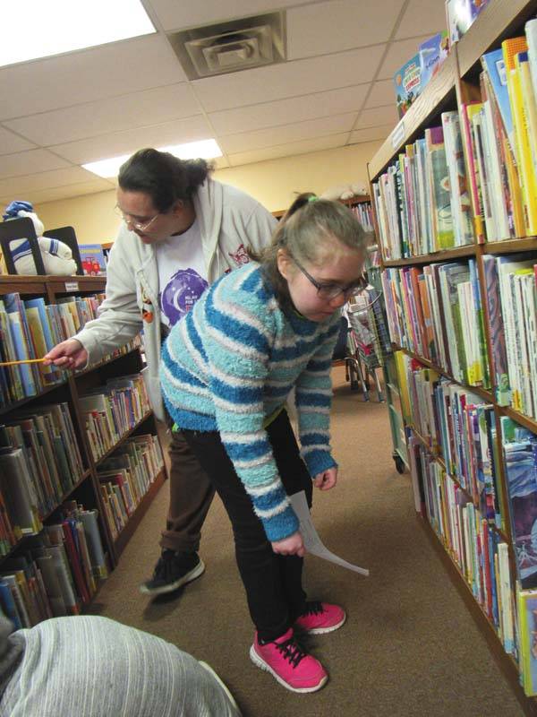 Gloversville resident Tammy Sweet-Chisam helps her stepdaughter Aliana Chisam, 10, during the library opening-day scavenger hunt. Youths who finish the hunt will be rewarded with a goodie bag of useful items, prizes and raffle tickets. (The Leader-Herald/Eric Retzlaff)
