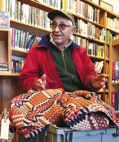 "Local history buff Willis ""Skip"" Barshied talks about the history of a vintage hand-woven coverlet (bedspread) that he presented to the Fort Plain Free Library for a fundraiser in support of Phase II construction. A raffle for that purpose kicked off at the 19 Willett Street library on Friday and Saturday during the annual Book, Bake and Plant Sale. (Photo submitted)"