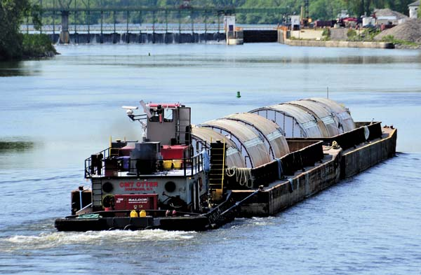 The first set of Genesee Brewery tanks headed for Rochester via the  Erie Canal  make their way on connected barges through Amsterdam to Lock E11. Two sets of barges, each carrying six 20-foot by 60-foot tanks, will make their way west 225 miles to Rochester. The journey will take about a week. The tanks are a key piece of a  $49 million renovation and modernization project  underway at the Genesee brewery. At right,  the barge is secured  in Lock E11. (The Leader-Herald/Bill Trojan)