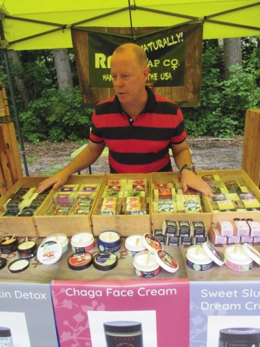 Dan Long, sales and business development coordinator of RAD  Soap Co., explains the origin and variety of soaps and lotions manufactured by the company in Menands Saturday at the Amsterdam Farmers Market opening day. (The Leader-Herald/Eric Retzlaff)