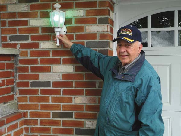 Johnstown resident Pat O'Lucci shows off one of the green lights outside his Elmwood Avenue home Thursday in commemoration of returning military veterans. (The Leader-Herald/Michael Anich)