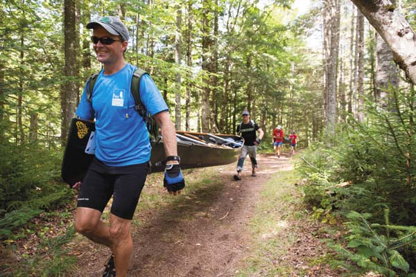 Paddlers carry canoes through the Marion River Carry during the 90-mile Adirondack Canoe Classic race. (Photo courtesy of Mike Lynch for Open Space Institute)