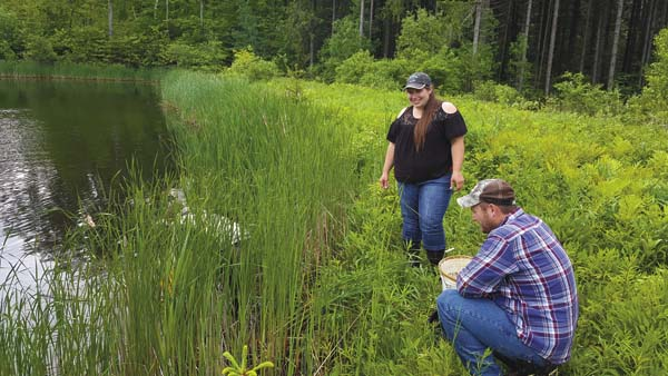 Montgomery County Soil and Water Conservation District technician Scott Davies, right, watches as Collin Sullivan, a NRCS intern and in the water, and Julicia Godbout, center, AED coordinator, stock the Burbine Forest pond. (Photo submitted)