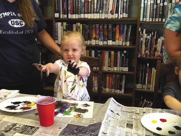 2-year-old Ava Miner had as much fun painting with her hands as  she did with a sponge.   (Photo submitted)