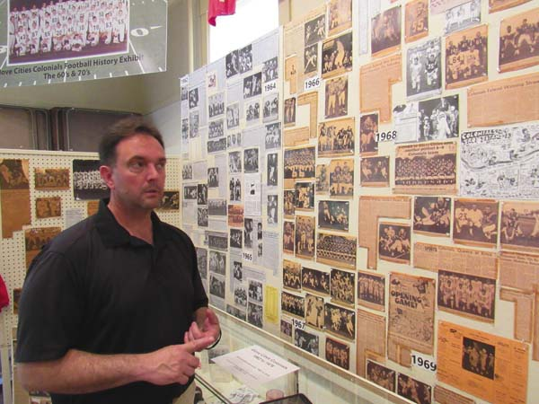 Mike Hauser, who organized the Glove Cities Colonials football team reunion Saturday at the Fulton County Museum, points out just one section of the 1960s and 1970s history of the team. (The Leader-Herald/Eric Retzlaff)