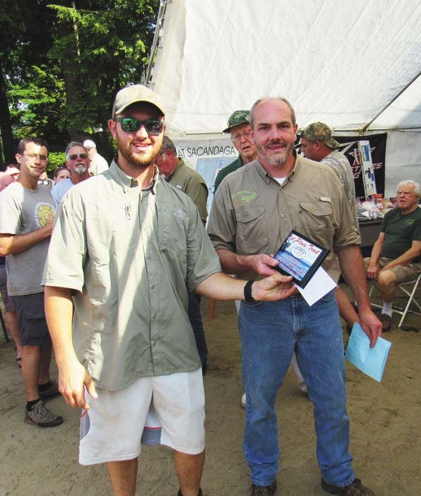 Randy Gardinier, coordinator of the 26th annual Summer Fishing Contest sponsored by Great Sacandaga Lake Fisheries Federation, hands a plaque and prize money to Forrest Higgins of Glenville for the first-place trout Saturday at the lake. (The Leader-Herald/Eric Retzlaff)