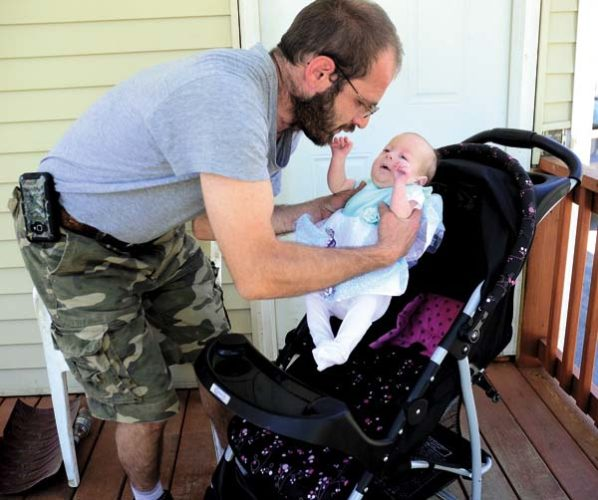 Kevin Bradt places his daughter, Sabrina, into her stroller outside their Gloversville home on Wednesday. (The Leader-Herald/Bill Trojan)