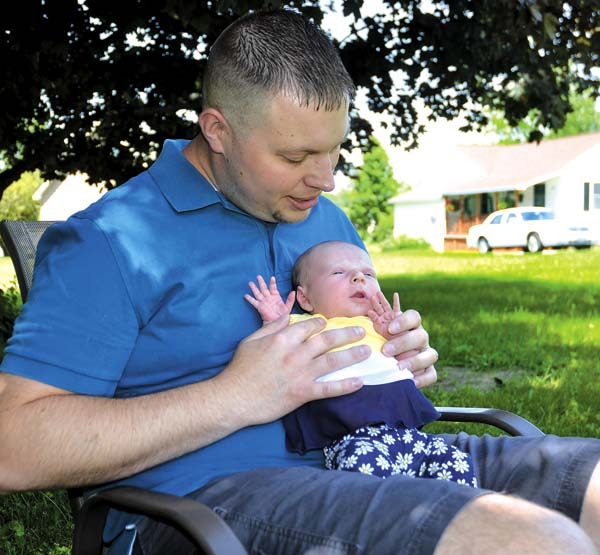 Bradley Hayner of Johnstown looks at his newborn daughter, Laila, outside their home on Thursday.  (The Leader-Herald/Bill Trojan)