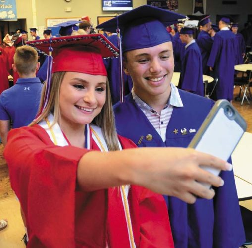 Isabella Bianca Magliocca, left, and Ryan Zajaceskowski take a selfie together in the lunch room prior to the commencement at the Broadalbin-Perth High School in Broadalbin on Friday. (The Leader-Herald/Bill Trojan)