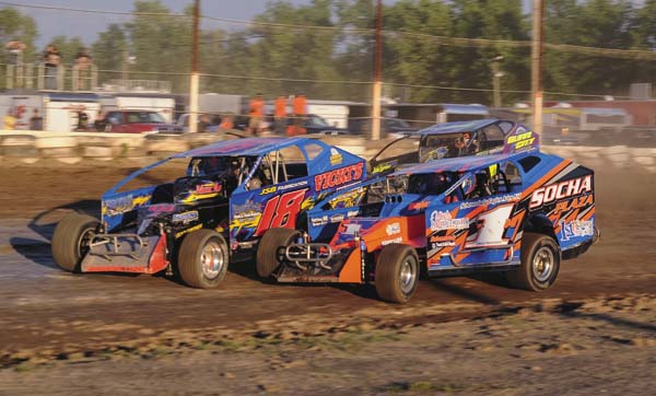 Tony Farone (18), Mark Mortensen (1M) and Rocky Warner race through turns three and four during sportsman action Saturday at Fonda Speedway. (The Leader-Herald/James A. Ellis)