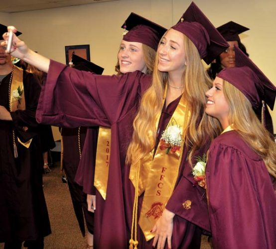 From left, seniors Julianna Taylor,  Juliet Mancini and Julia Viscosi take  smartphone photo together prior to the Fonda-Fultonville High School Commencenment on Saturday. (The Leader-Herald/Bill Trojan)