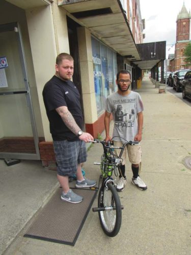Outside The Randy Shop at 15 Bleecker St., Randy Rose, left, and Tyrell Adams display the bicycle and lock set Rose gave to Adams after Adams's bike was stolen in front of the temporary Gloversville library on June 12. (The Leader-Herald/Eric Retzlaff)