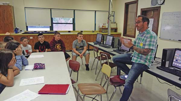 Parent Nate Snow, an accountant, talks to sixth-grade students Sam Kosiba, Landon Rose, Owen Hicks and Tyler Couture. (Photo submitted)