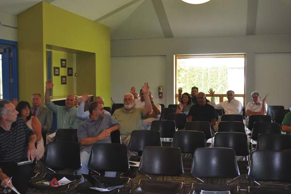 Members of the Montgomery County Shared Services Panel raise their hands in support of the county's plan to save taxes through shared services and consolidation Wednesday at Fulton Montgomery Community College. (The Leader-Herald/Jason Subik)
